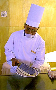 Chef at Melia Cabo San Lucas Resort Hotel prepares an omelette for breakfast wearing a mask as required by law